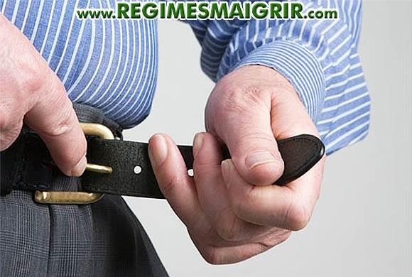 Un homme est en train de relâcher sa ceinture