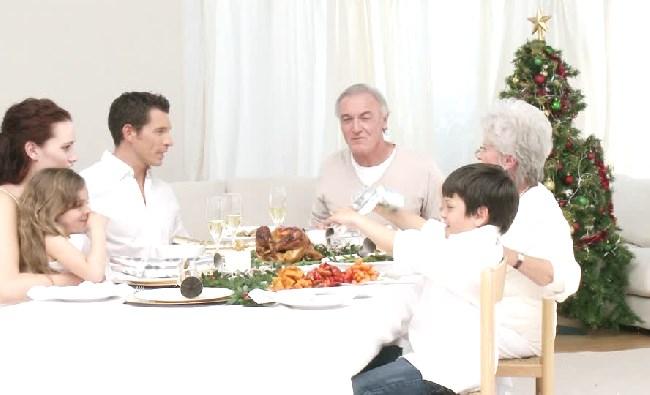 Une famille mange ensemble à côté du sapin de Noël