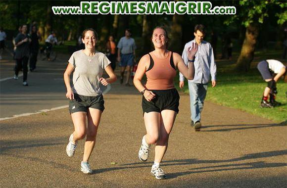 Deux femmes courent ensemble dans un parc tout en souriant