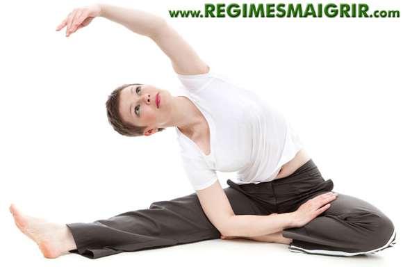 Femme en train de faire des étirements et de l'exercice en s'asseyant par terre