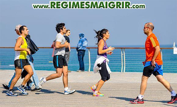 Des hommes et des femmes sont en train de faire du jogging près d'une plage pavée en bois