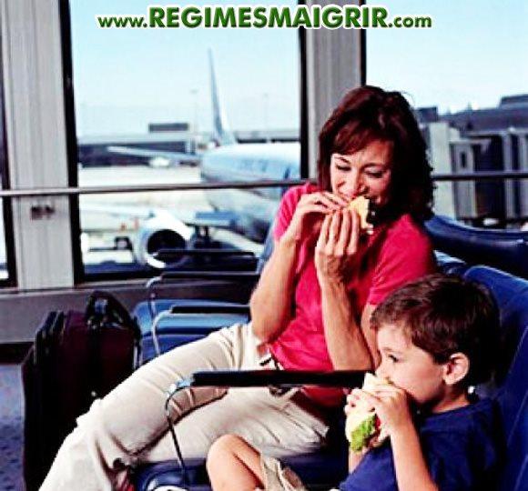 Une mère et son enfant dégustent chacun un sandwich en attendant un vol à l'aéroport