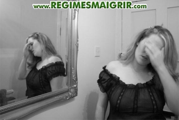 Une femme se tient le visage avec sa main en étant dépitée devant un miroir, probablement mécontente de sa propre perception