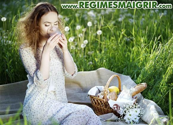 Une femme boit un verre de lait assise sur une nappe sur laquelle se trouve un panier pique-nique