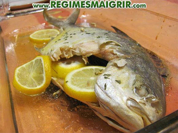 Un trachinotus floridien est cuit au four avec des tranches de citron dans son ventre