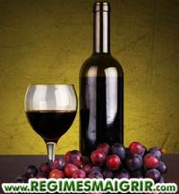 Une bouteille de vin rouge mise à côté d'un verre à moitié plein et des raisins rouges