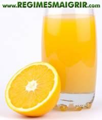 Un verre de jus d'orange frais posé à côté de cet agrume