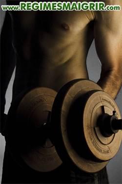 Homme en train de lever un haltère pour effectuer l'un des mouvements de musculation les plus simples qui soient