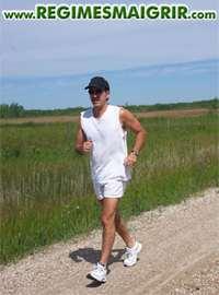 Un sportif en train de jogger sur un petit chemin à côté des champs