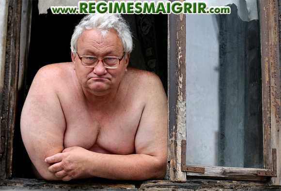 Un homme âgé et présentant une surcharge pondérale debout devant une fenêtre