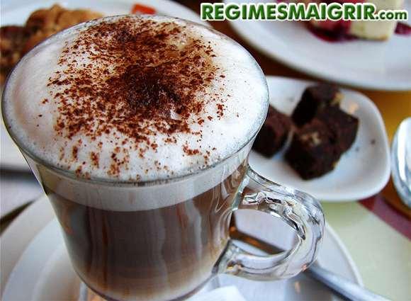 Une tasse de cappuccino posée sur la table à côté de diverses assiettes de chocolat et de gâteaux