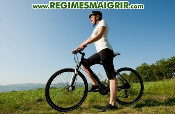 Une jeune femme est debout sur son vélo sur un chemin herbeux sous le soleil