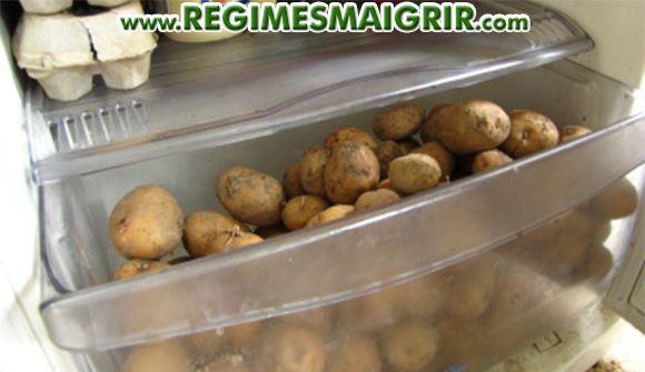 Des pommes de terre conservées dans le bac à légumes d'un réfrigérateur blanc