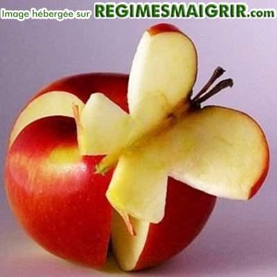 Un papillon est joliment sculpté dans une pomme rouge