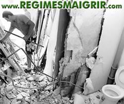 Un maçon détruit les murs et cloisons pour dégager la voie de sortie