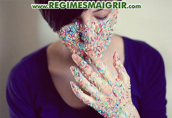 Une femme a le visage collé d'une multitude de petits morceaux de bonbons multicolores