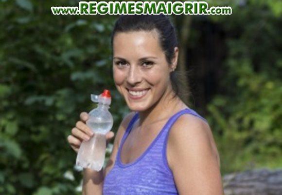 Une femme porte une bouteille d'eau à la bouche