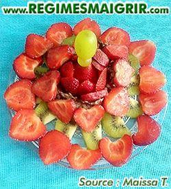 Des fraises sont coupées en deux et agencées de belle manière sur des tranches de kiwis le tout surmonté par quelques raisins et posé dans une assiette ronde