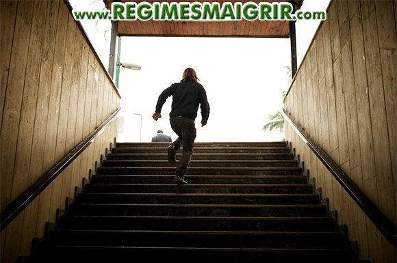 Une personne à la chevelure blonde monte les escaliers en courant