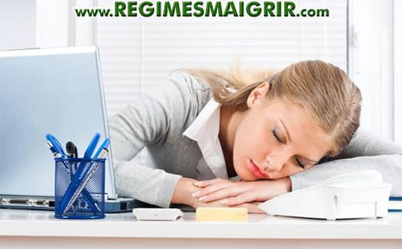 Une femme est fatiguée et s'affale sur son bureau afin de se reposer
