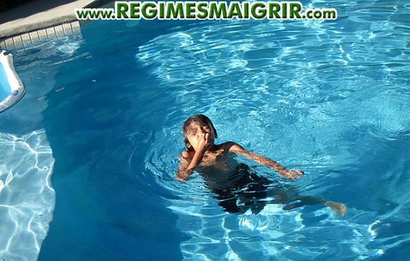 Un jeune garçon est en train de nager dans une piscine familiale