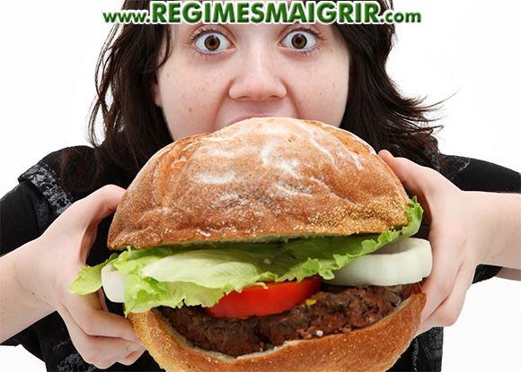 Une femme dévore littéralement un hamburger en s'écarquillant des yeux