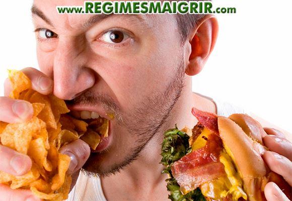 Un homme avale tout ce qu'il tient dans les mains à savoir des chips et un sandwich gras et calorique