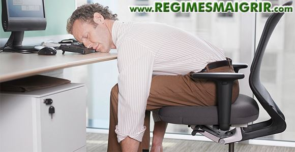 Un employé de bureau est si fatigué qu'il dort sur sa table