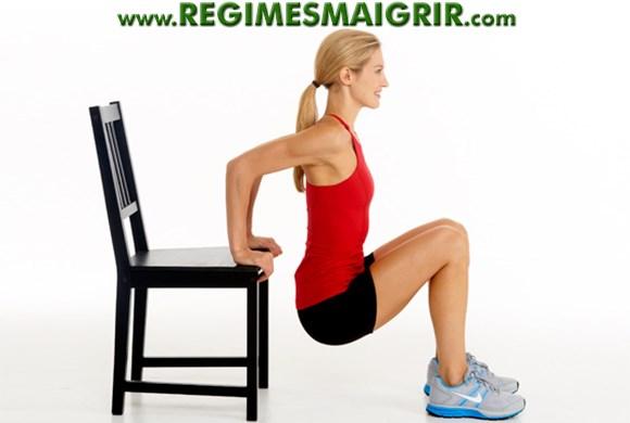 Une femme est en train de réaliser l'exercice au poids du corps dips
