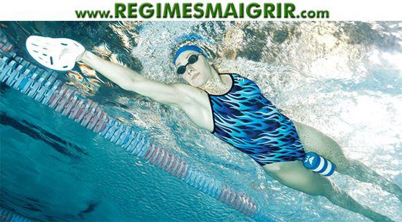 Une nageuse fixe ses pieds avec un pull-buoy pour nager uniquement avec les bras