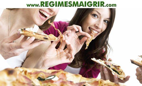 Un groupe d'amies dégustent ensemble des tranches de pizza dans le cadre d'un repas d'écart