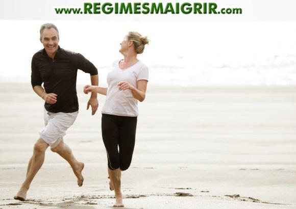 Deux quadragénaires courent ensemble pieds nus sur une plage