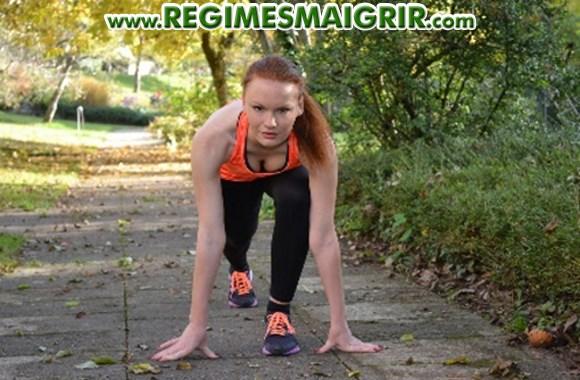 Une jeune femme fait de l'exercice sur un chemin apparemment situé dans un parc
