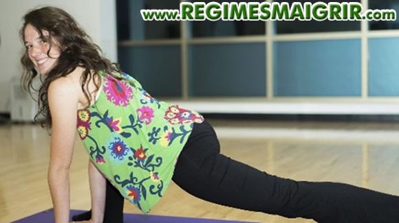 Une femme rigole en faisant du fitness en mode circuit training sur un tapis posé par terre