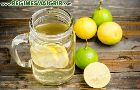 Un bocal d'eau citronnée est posé sur la table à côté des citrons frais