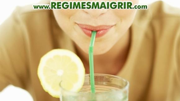 Une jeune femme boit de l'eau citronnée avec une paille