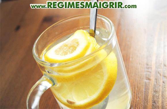 Une cuillère est posée dans un verre d'eau contenant du citron