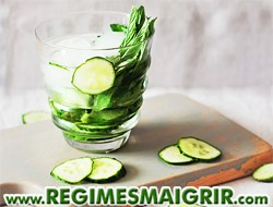 Une potion contenant des morceaux de concombre et des feuilles de menthe