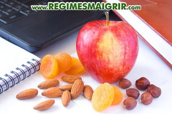 Des fruits secs posés sur une table de travail à côté des noix et une pomme fraîche