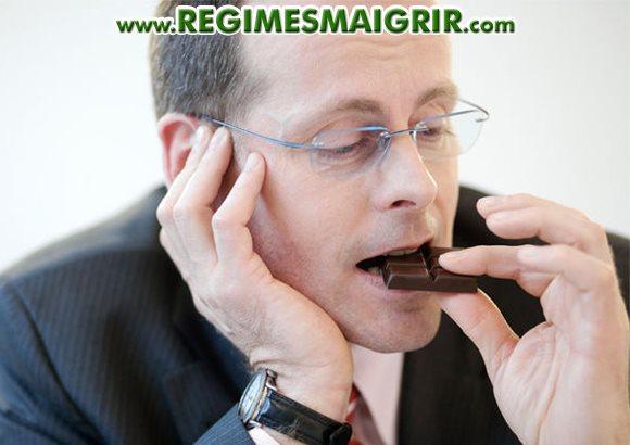 Un homme d'affaire déguste des carrés de chocolat