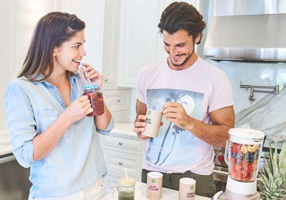 Un homme et une femme boivent des compléments alimentaires sous forme de shake dans une cuisine