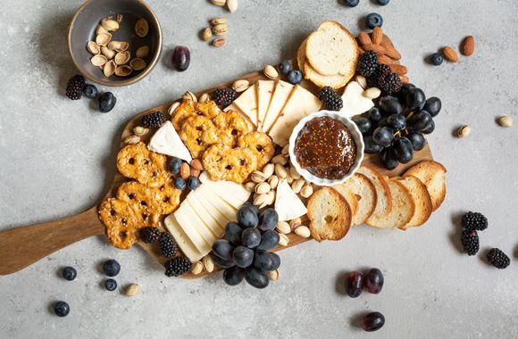 Un plateau de fromages avec des raisins noirs, des myrtilles, des crackers, des amandes et du pain