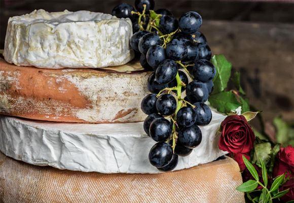 Une grappe de raisins noirs posée sur une pile de fromages et à côté de deux roses rouges