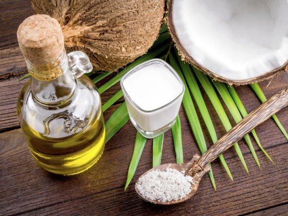 Une bouteille d'huile de coprah à côté d'extraits de noix de coco et des feuilles de cocotier
