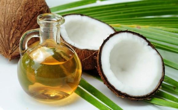 Une bouteille d'huile de noix de coco mise à côté de quelques fruits du cocotier