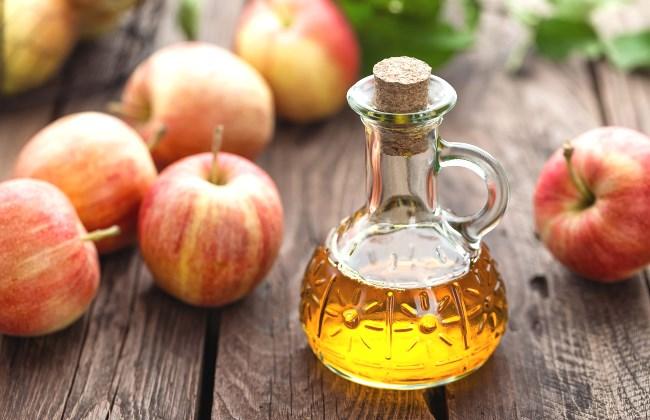Une bouteille de vinaigre de cidre posée à côté des pommes