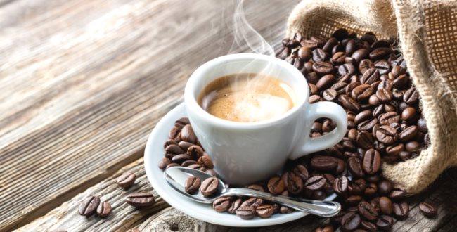 Une petite tasse de café posée à côté de dizaines de grains du même aliment