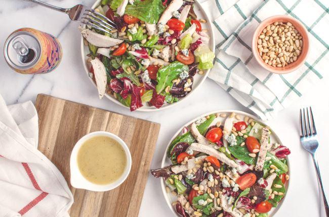 Assiettes de salades mises sur la table à côté d'une canette de boisson