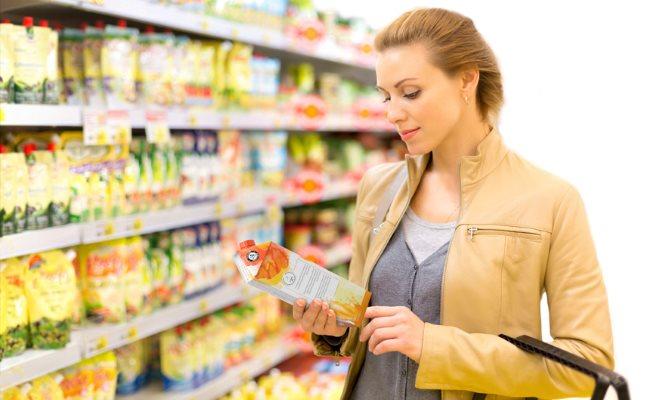 Une jeune femme est en train de lire les informations nutritives sur l'étiquette d'un paquet alimentaire