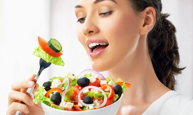 Une jeune femme est en train de déguster un bol de salades